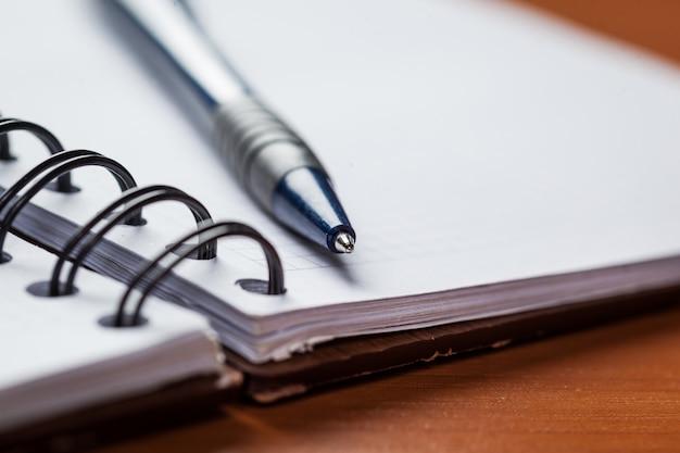 Papier vierge avec un stylo sur fond de bois