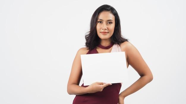Papier vierge vide dans la main de la femme asiatique. un portrait en studio avec un fond blanc. un espace vide pour le texte. elle a la peau bronzée.