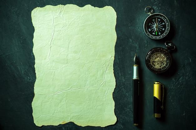 Papier vintage et stylo avec boussole et montre de poche sur fond noir.
