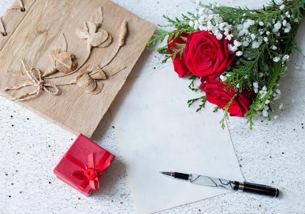 Papier vintage et stylo pour écrire avec un cadeau et des roses