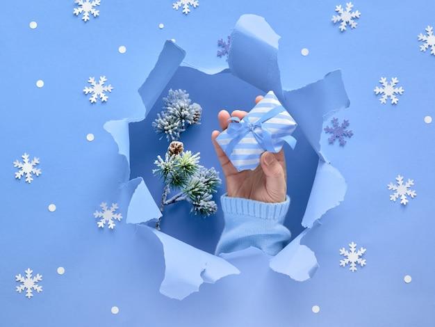 Papier violet lavande à plat avec la main avec un cadeau, des flocons de neige et un trou déchiré
