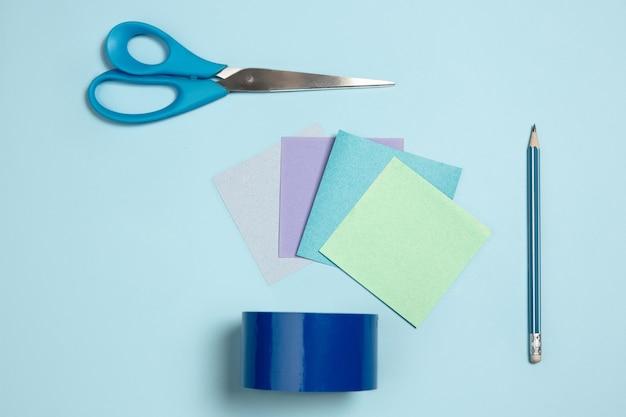 Papiers autocollants ciseaux stylo composition élégante monochrome en vue de dessus de couleur bleue mise à plat