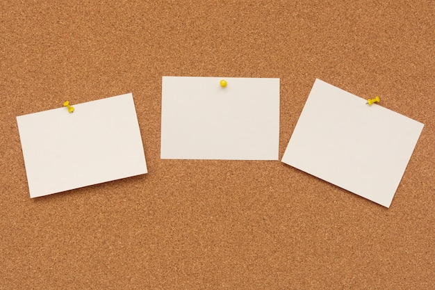 Papiers à billets rayés avec punaises sur un tableau en liège