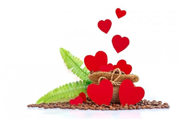 Papiers coeur sur sac de jute de café avec feuille verte et grain de café