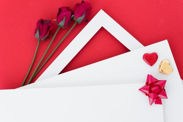 Papiers avec coeurs d'ornement et arc près des fleurs