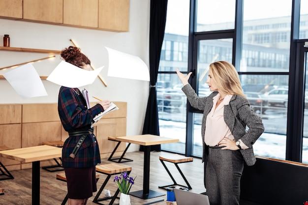 Papiers dans l'air. patron féminin strict aux cheveux blonds mettant des papiers dans l'air se sentant insatisfait et en colère
