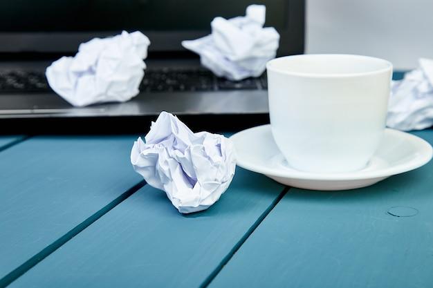 Papiers émiettés au travail avec un ordinateur portable