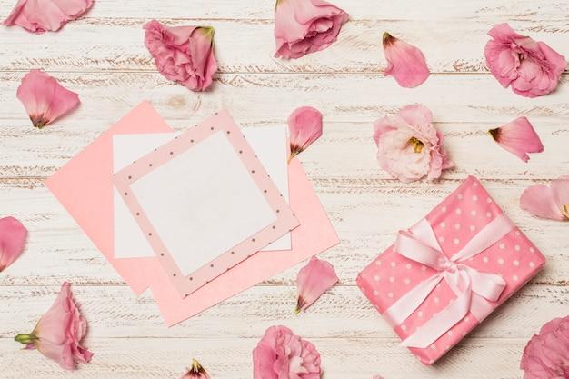 Papiers entre les fleurs près de la boîte-cadeau