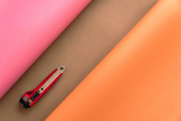 Papiers rose et orange se penchant sur le brun sous forme abstraite avec un cutter rouge