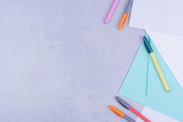 Papiers vierges et crayons multicolores sur gris.