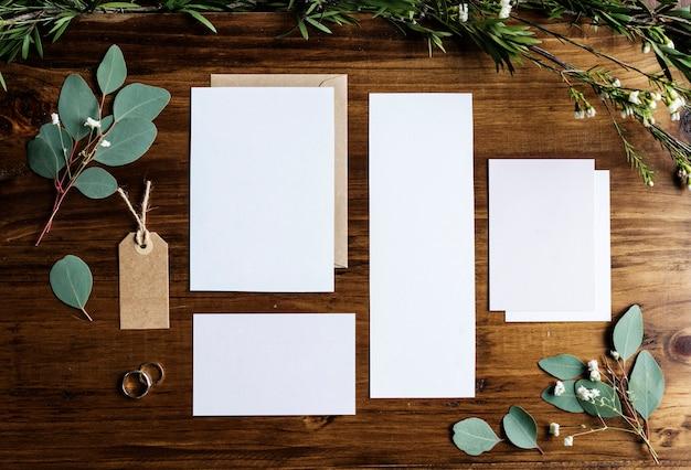 Papiers vierges posant sur une table en marbre avec décoration de feuilles