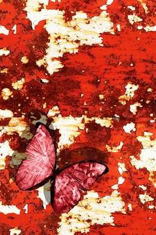Un papillon rouge est assis sur un mur en métal texturé. photo de haute qualité