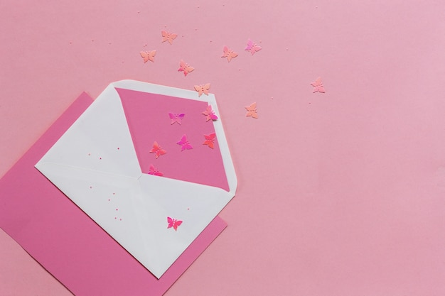 Papillons roses dans l'enveloppe rose sur le papier rose