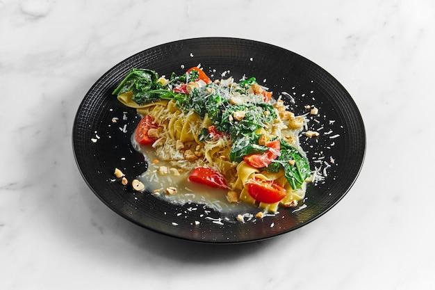 Pappardelle au panais, sauce à la crème, verts blanchis, tomates et noix sur une plaque noire sur fond blanc