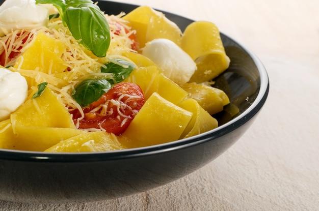 Pappardelle de pâtes cuites jaunes, fettuccine ou tagliatelles close up