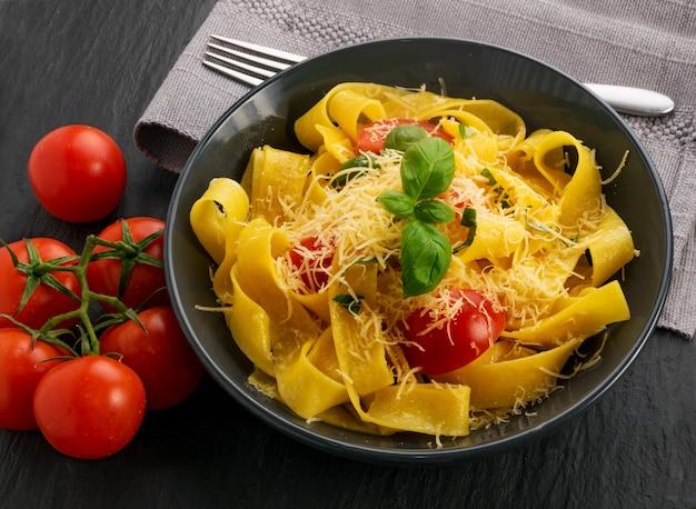 Pappardelle de pâtes cuites jaunes, fettuccine ou tagliatelles en vue de dessus de bol noir.