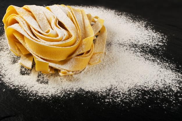 Pappardelle de pâtes italiennes jaunes crues, fettuccine ou tagliatelles close up