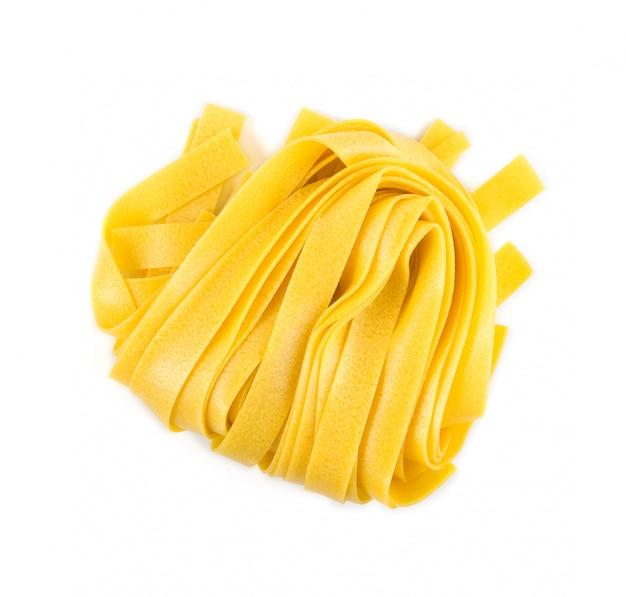 Pappardelle de pâtes italiennes jaunes crues, fettuccine ou tagliatelles se bouchent.