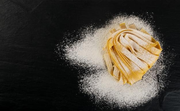 Pappardelle de pâtes italiennes jaunes crues, fettuccine ou vue de dessus de tagliatelles.
