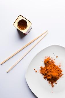 Paprika sur assiette blanche, deux baguettes et un pot sur fond blanc