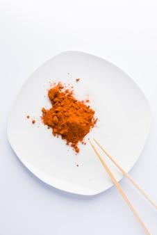 Paprika sur assiette et deux baguettes sur fond blanc