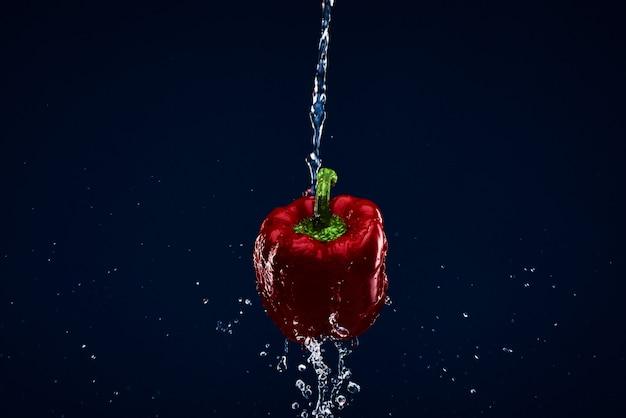 Paprika rouge doux isolé lavé sous l'eau.