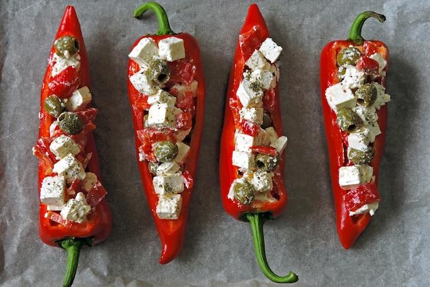 Paprika rouge farci de feta et d'olives avant cuisson. cuisson des poivrons avec du fromage feta.