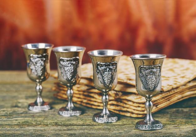 Pâque fond quatre verres vin et pain de fête juif matzoh sur planche de bois.