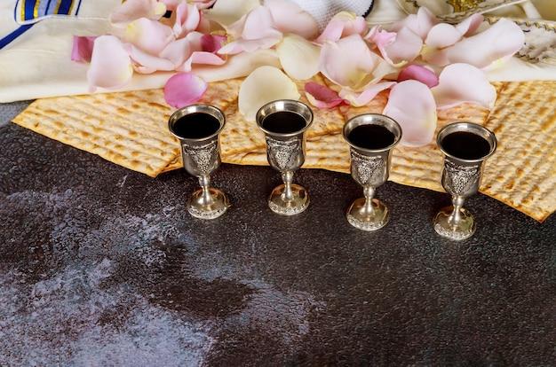 Pâque haggadah une fête juive matzo quatre verres tasse de vin rouge casher sur talit et kippa