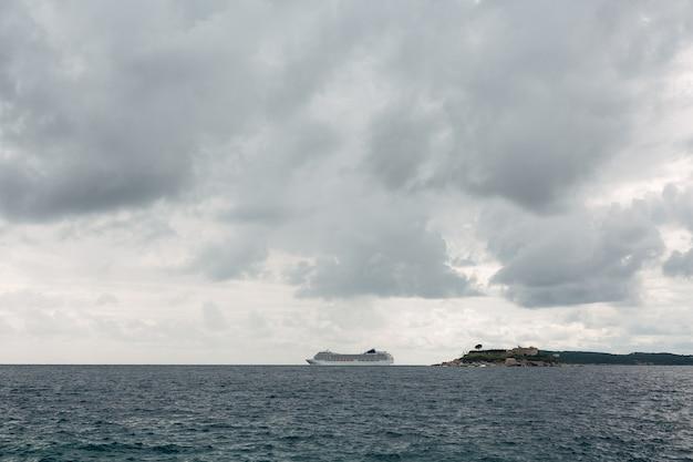Paquebot de croisière à l'horizon, près de l'île de mamula au monténégro. contre le ciel nuageux avec des nuages gris. photo de haute qualité
