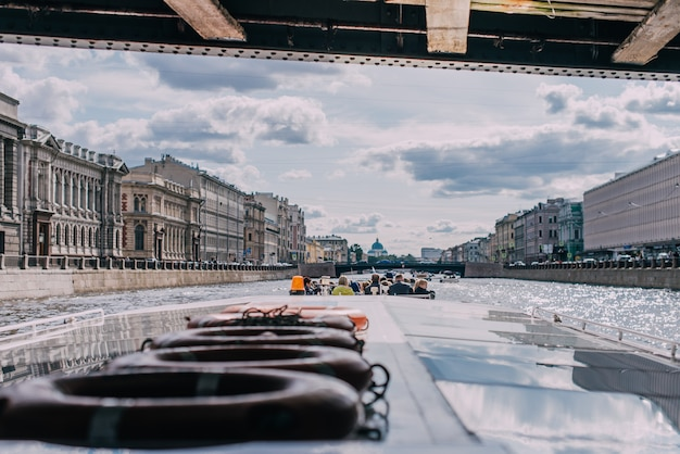 Paquebot avec passagers passe sous le pont sur la rivière fontanka