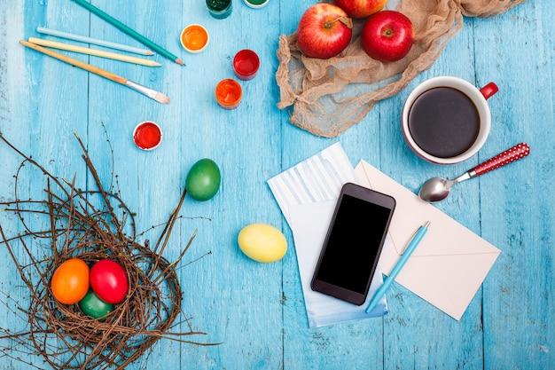 Pâques au travail de bureau sur une table en bois bleue.