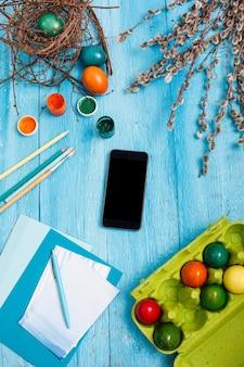 Pâques au travail de bureau sur une table en bois bleue