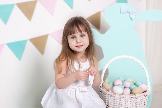 Pâques! belle petite fille dans une robe blanche avec des oeufs de pâques et un panier sur un paysage lumineux de pâques. lieu de pâques, décorations. vacances en famille, traditions. chambre colorée. développement de l'enfant.