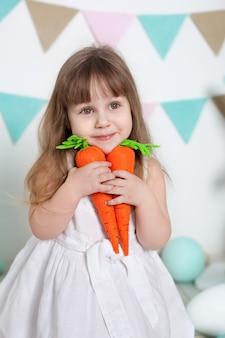 Pâques! belle petite fille en robe blanche assise avec des lapins de pâques et des carottes. beaucoup d'oeufs de pâques colorés différents, intérieur de pâques coloré. agriculture. enfant et jardin. printemps. récolte