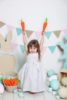 Pâques! belle petite fille en robe blanche assise avec des lapins de pâques et des carottes. lapin et oeufs colorés. beaucoup d'oeufs colorés différents, intérieur coloré de pâques. agriculture. enfant et jardin.