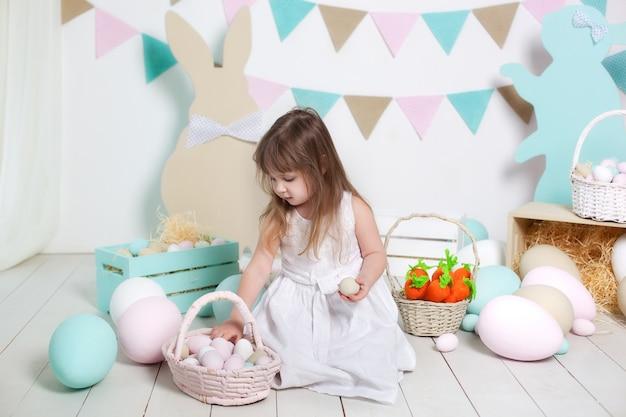 Pâques. belle petite fille en robe blanche dépose des oeufs de pâques dans un panier. beaucoup d'oeufs de pâques colorés différents, intérieur coloré. lapin de pâques, carotte et drapeaux colorés. intérieur et décoration. agriculteur