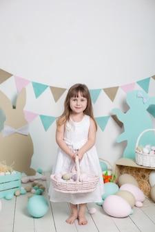 Pâques! belle petite fille en robe blanche avec des oeufs de pâques et un panier sur un paysage de pâques lumineux. lieu de pâques, décorations. vacances en famille, traditions. développement de l'enfant. agriculteur. récolte