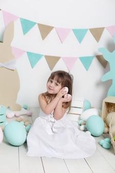 Pâques. belle petite fille vêtue d'une robe blanche détient des oeufs de pâques. gros oeufs multicolores dans un panier et des lapins de pâques. récolte, petit fermier. décoration de pâques, décor de printemps. vacances en famille.