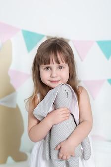 Pâques! belle petite fille vêtue d'une robe blanche embrasse un lièvre jouet. intérieur coloré de pâques. enfant joue avec un jouet. l'enfant reçoit un cadeau et profite des vacances. visage closeup portrait petite fille.
