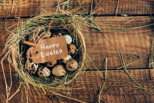 Pâques bio. vue de dessus des œufs de caille allongés dans un bol avec du foin avec une étiquette de pâques sur une table rustique en bois