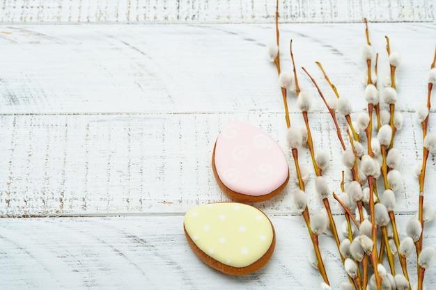 Pâques. branches de saules chatte ruban jaune et lièvres en pain d'épice de pâques, poulets et œufs