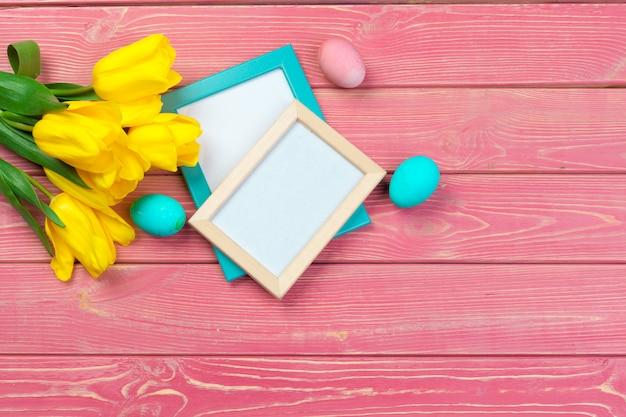 Pâques . cadre en bois avec des oeufs de pâques et des tulipes sur coloré