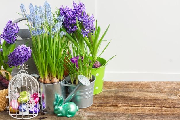 Pâques dans les oeufs de jardin en cage à oiseaux et lapin avec des pots de fleurs, espace copie sur table en bois