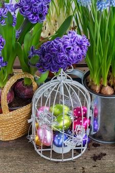 Pâques dans les oeufs de jardin en cage à oiseaux avec des pots de fleurs