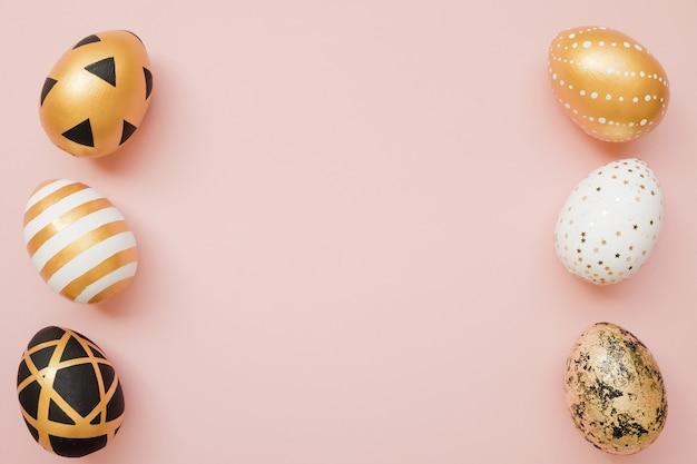 Pâques doré décoré d'oeufs sur fond rose pastel. pâques minime