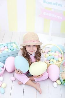 Pâques! fille détient de gros œufs multicolores dans ses mains sur le fond de l'intérieur de pâques. un bébé mignon court après les œufs de pâques. décoration de pâques. enfant et jardin. petit fermier. récolte