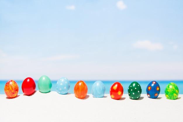 Pâques sur fond de plage tropicale. oeufs sur le sable blanc. concept de vacances et de voyage au printemps