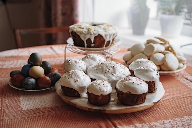 Pâques fraîche avec des gâteaux de garniture de sucre sur une grande assiette oeufs colorés sur fond