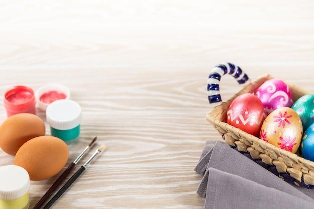 Pâques multicolores peints à la main des œufs, des peintures et des pinceaux.
